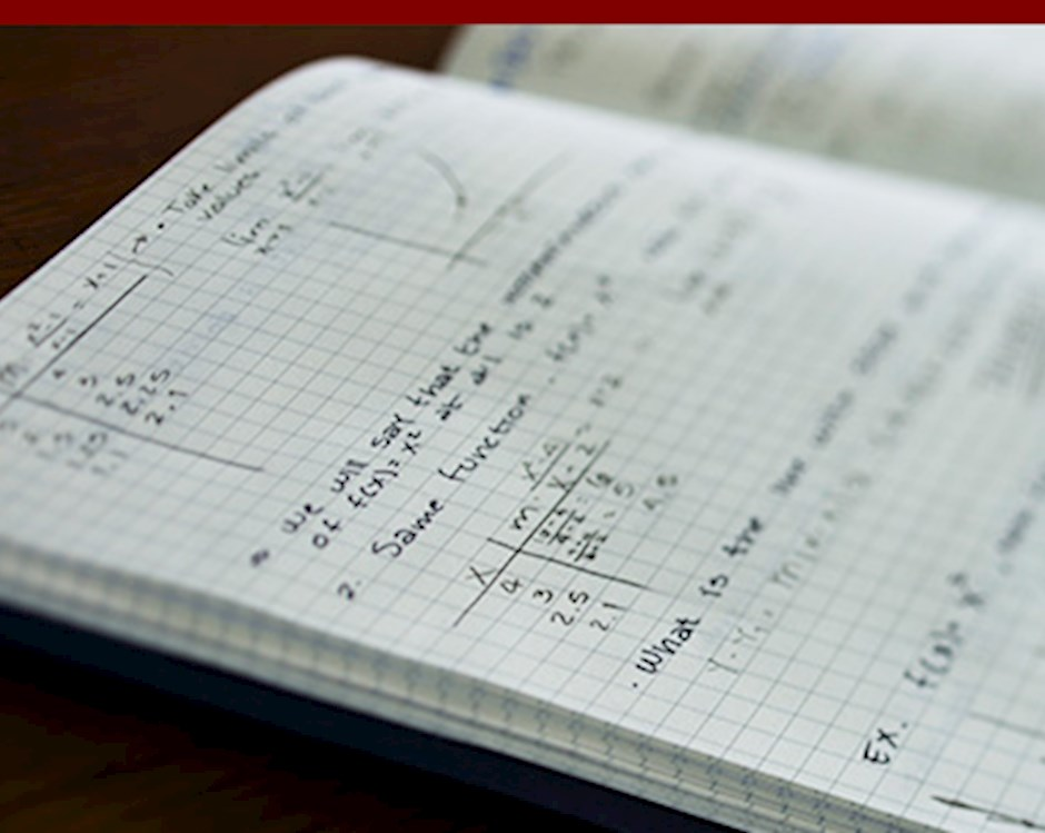 Close up of a grid notebook filled with math problems