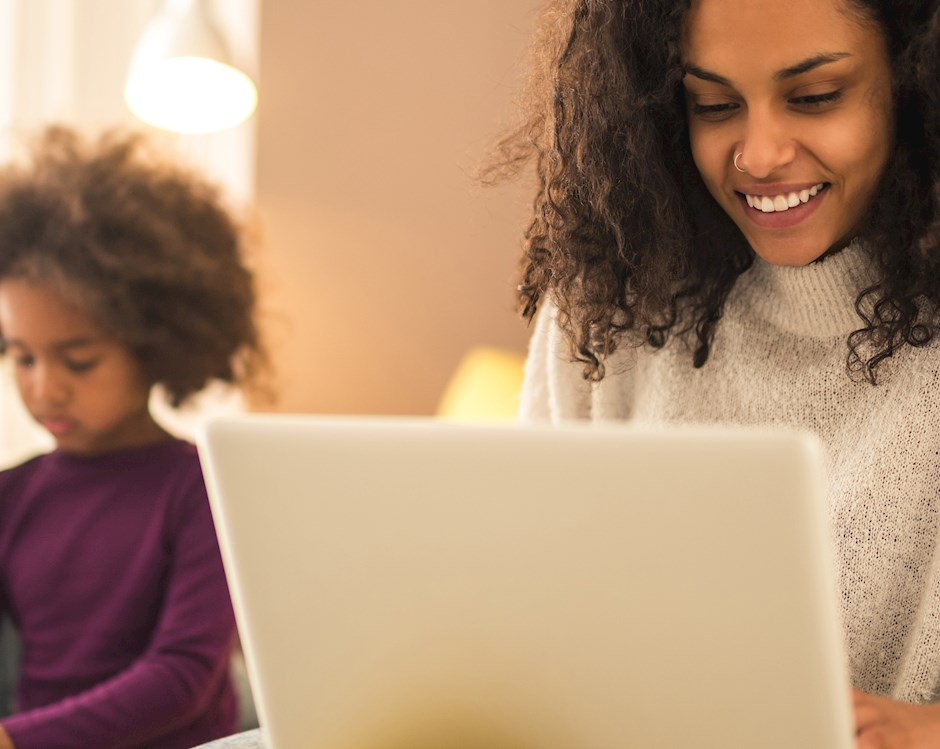 woman-using-laptop-family-in-background.jpg