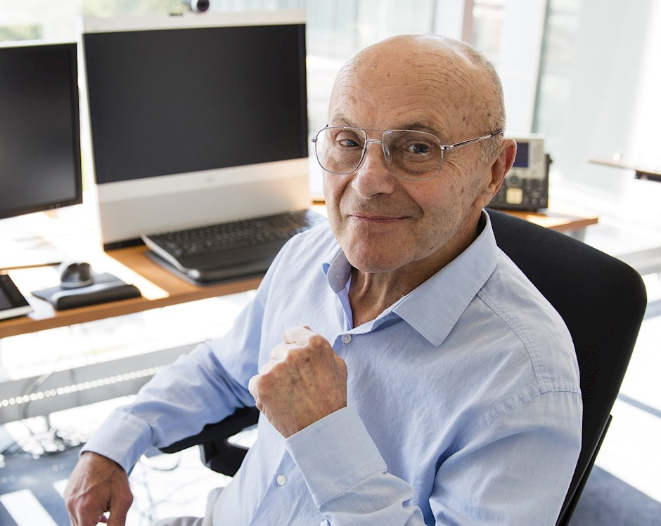 2013 Nobel Laureate in Economic Sciences Eugene Fama, an older man with button-down blue shirt, smiles while sitting at his desk.